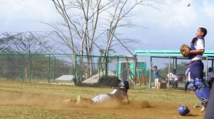 Fiji center fielder Semi Bolatini slides in safe at home