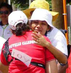 After a close finish, archery competitors Pualele Atoa-Craig (SAM) and Isabelle Soero (NC) embrace
